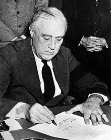 President Franklin Delano Roosevelt Signing Declaration of War Against Japan. December 8,1941. Photo by Office of War Information.